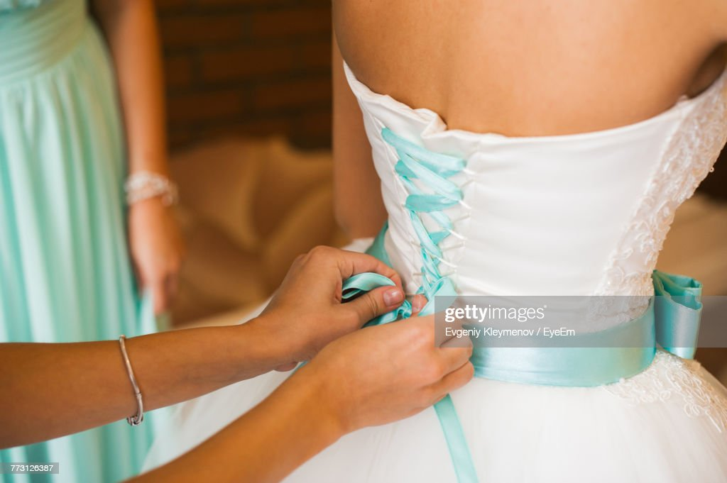 Close-Up Of Woman Assisting Bride For Getting Dressed : Photo