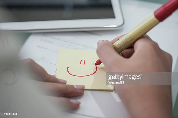 Close-up of woman at desk drawing a smiley face on sticky note