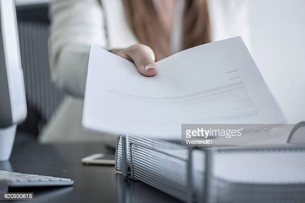 Close-up of woman at desk handing over a document