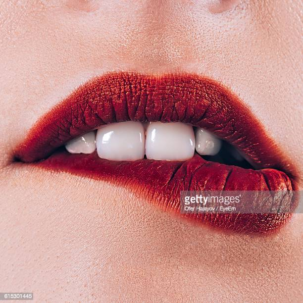 close-up of woman biting lips - biting lip stock pictures, royalty-free photos & images