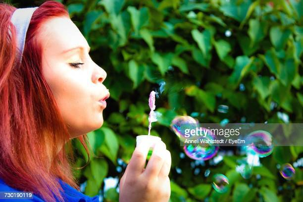 Close-Up Of Woman Blowing Bubbles Using Wand
