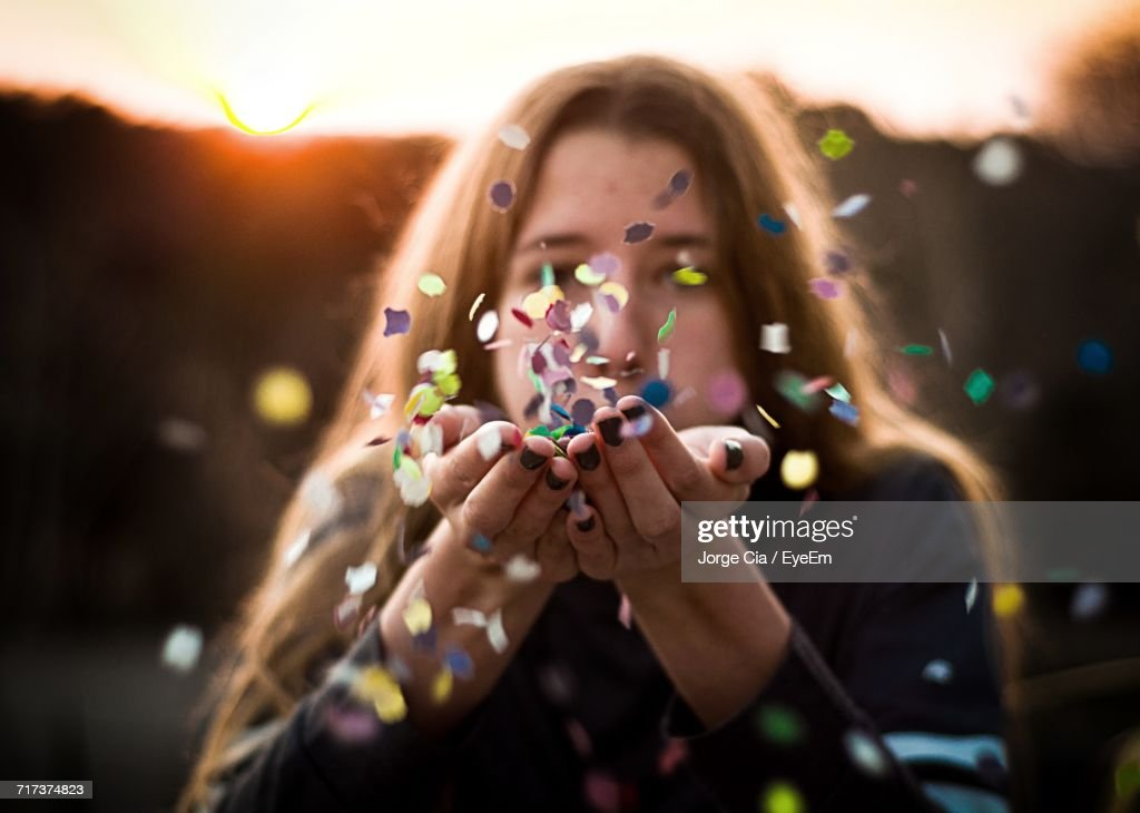 Close-Up Of Woman Blowing Confetti : Stock Photo