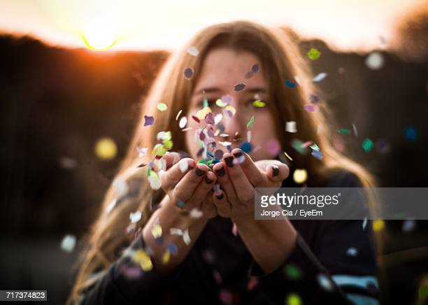 Close-Up Of Woman Blowing Confetti
