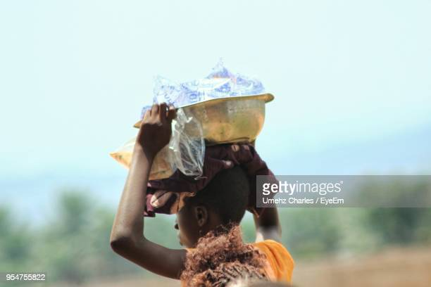 close-up of woman carrying container against sky - nigeria stock pictures, royalty-free photos & images