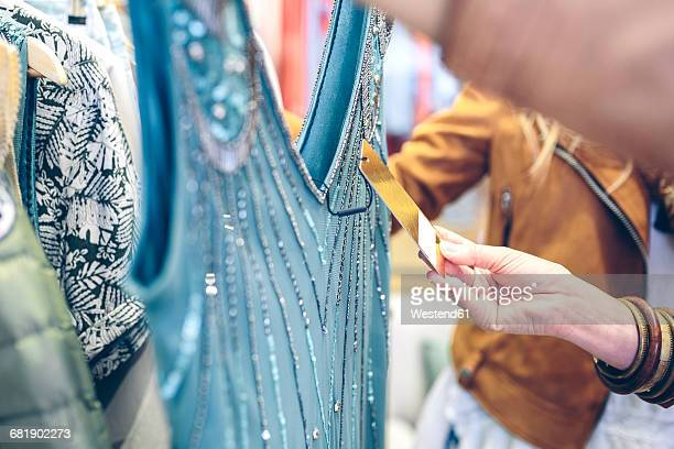 Close-up of woman checking price tag of a dress in a boutique