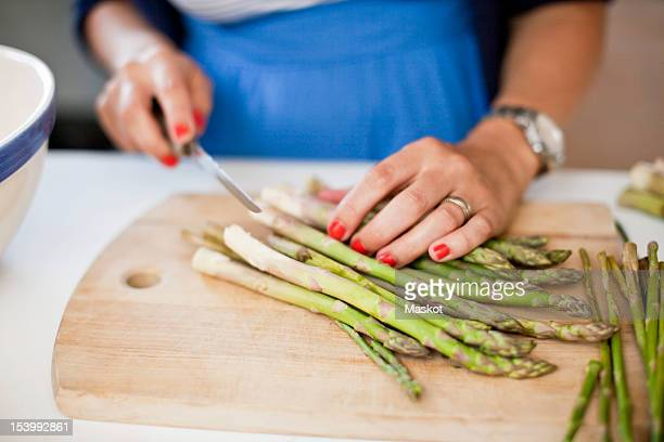 close-up of woman chopping asparagus on cutting board - asparagus stock pictures, royalty-free photos & images