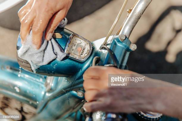 Close-up of woman cleaning vintage motorcycle