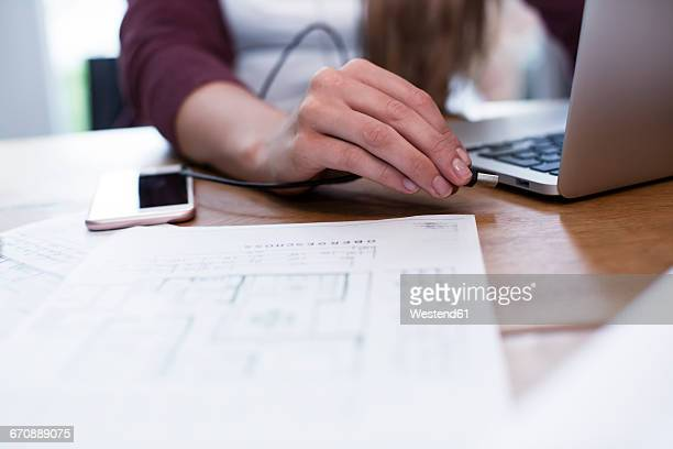 Close-up of woman connecting usb stick to laptop