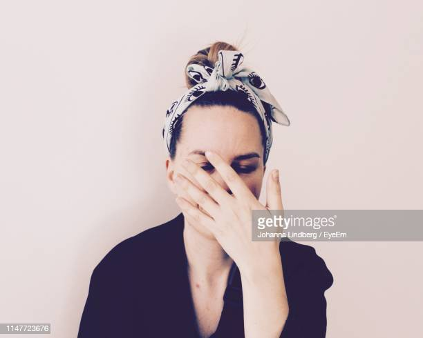 close-up of woman covering face against wall - obscured face stock pictures, royalty-free photos & images
