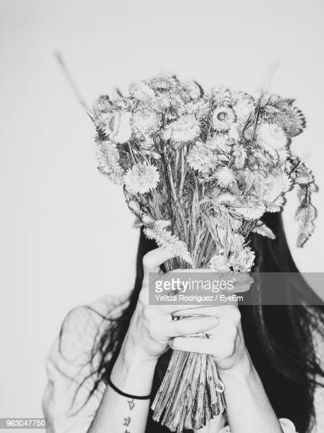close-up of woman covering face with bouquet against wall - art bildbanksfoton och bilder