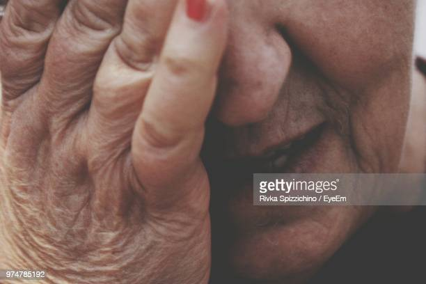 Close-Up Of Woman Covering Face With Hand