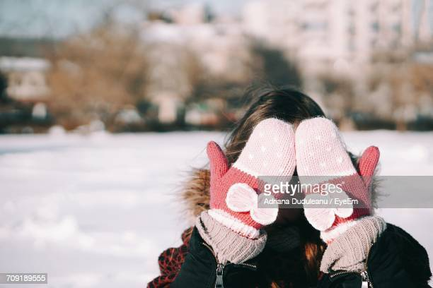 close-up of woman covering her face - mitten stock photos and pictures