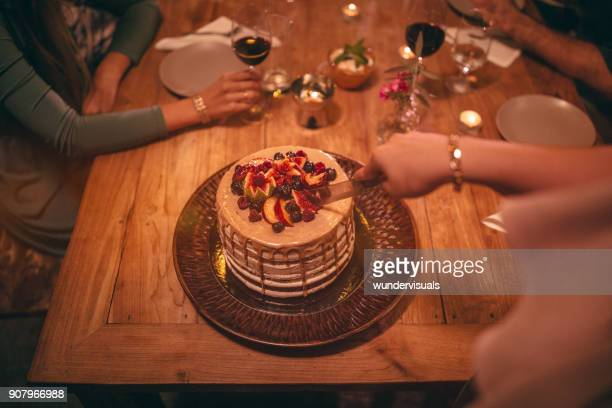 Close-up of woman cutting gourmet dessert at rustic dinner party