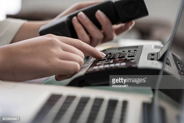 close-up of woman dialing a telephone number in office - telephone number stock pictures, royalty-free photos & images