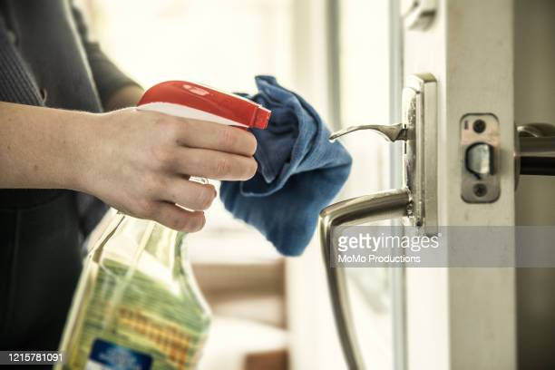 close-up of woman disinfecting door handle with spray bottle - prevention - fotografias e filmes do acervo