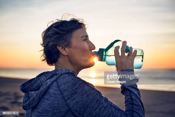 close-up of woman drinking water at beach against sky - drinking water stock pictures, royalty-free photos & images
