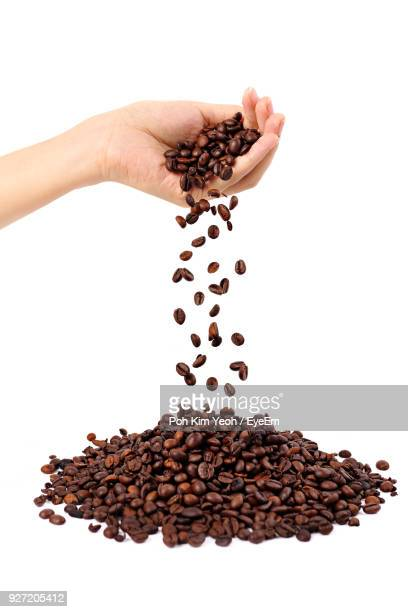 Close-Up Of Woman Dropping Roasted Coffee Beans Over White Background
