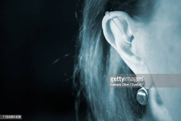 close-up of woman ear with hearing aid against black background - ear canal stock-fotos und bilder