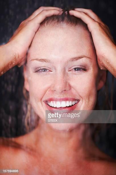 Gros plan de femme appréciant une douche sur fond sombre