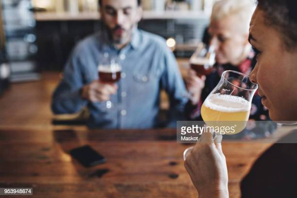 Close-up of woman examining craft beer while sitting with friends at bar