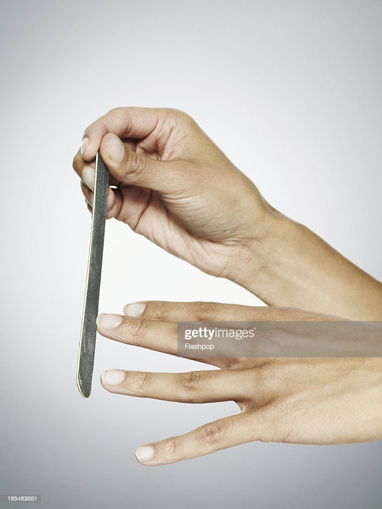 Close-up of woman filing her nails : Stock Photo