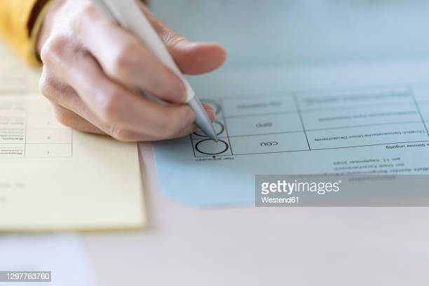 close-up of woman filling voting ballot at home - election stock-fotos und bilder