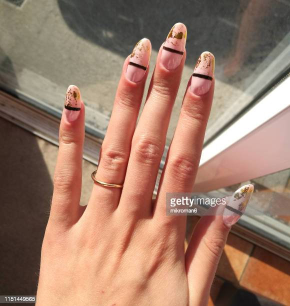 close-up of woman fingers with nail art manicure in nude colour - nail art stock pictures, royalty-free photos & images