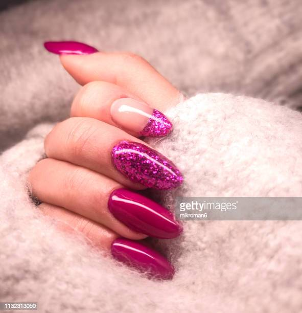 close-up of woman fingers with nail art manicure in pink colour for new years party - fingernail stock pictures, royalty-free photos & images