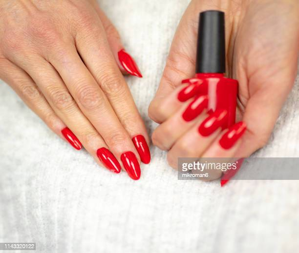 close-up of woman fingers with nail art manicure in red color - nail salon stock pictures, royalty-free photos & images