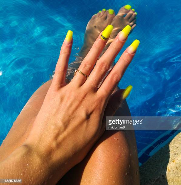 Close-Up Of Woman Fingers With Nail Art Manicure with Neon Green Colour in a Swimming Pool