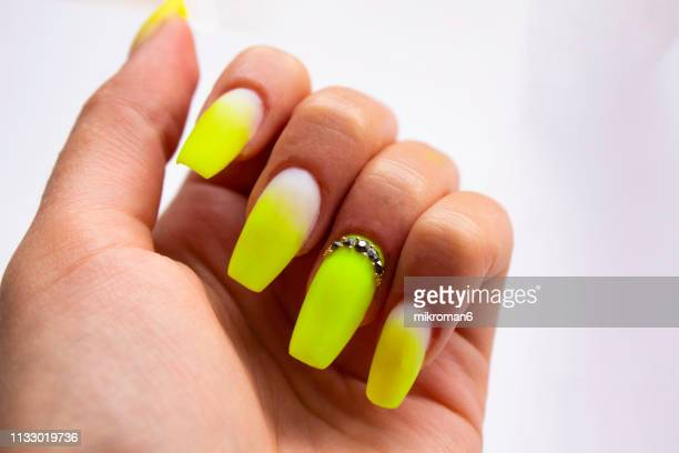 close-up of woman fingers with nail art manicure with neon green colour - nail art stock pictures, royalty-free photos & images