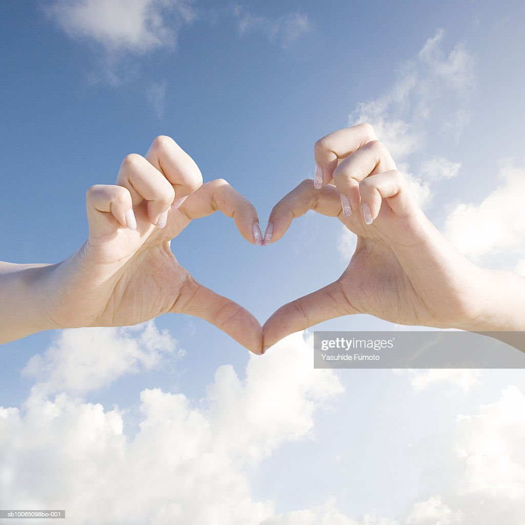Close-up of woman forming heart shape with hands against sky background : Stock Photo