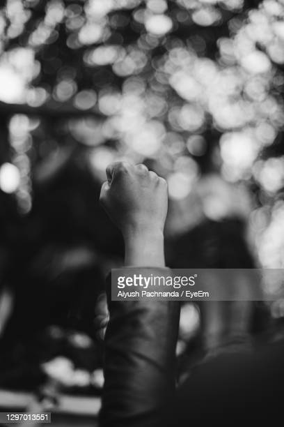 close-up of woman gesturing clenched fist against blurred background outdoors - striker stock pictures, royalty-free photos & images