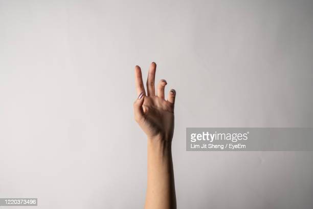 close-up of woman hand against white background - hand raised stock pictures, royalty-free photos & images