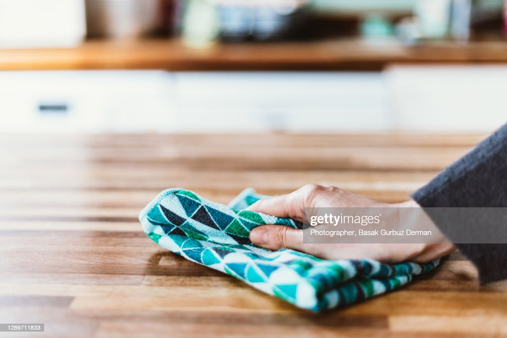 Close-up of woman hand cleaning the surface of a table with a cleaning cloth at home : Stockfoto