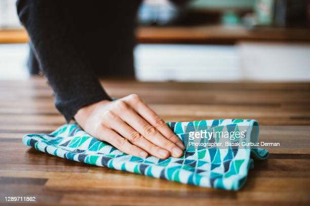 close-up of woman hand cleaning the surface of a table with a cleaning cloth at home - table stock pictures, royalty-free photos & images