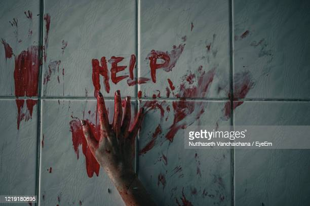 close-up of woman hand covered with blood by help text on wall - female torture stock pictures, royalty-free photos & images