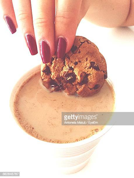 Close-Up Of Woman Hand Dipping Chocolate Chip Cookie Into Tea