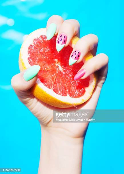 close-up of woman hand holding citrus fruit - nail art stock pictures, royalty-free photos & images