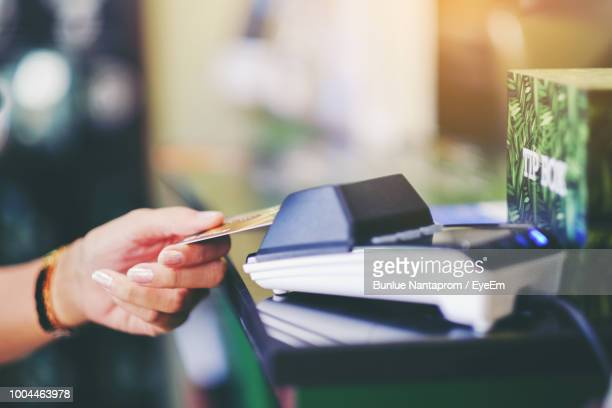 Close-Up Of Woman Hand Holding Credit Card While Making Payment In Store