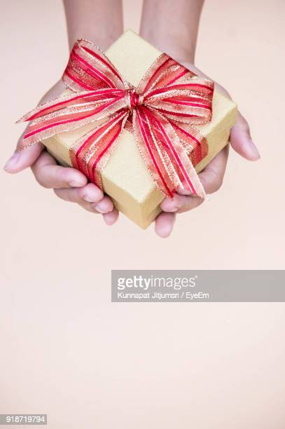 Close-Up Of Woman Hand Holding Gift Over White Background