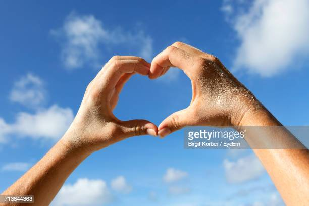 Close-Up Of Woman Hand Holding Heart Shape On Beach Against Sky
