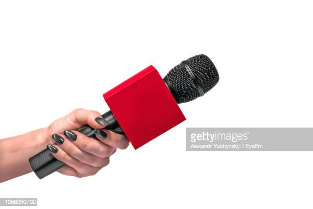 close-up of woman hand holding microphone against white background - micrófono fotografías e imágenes de stock
