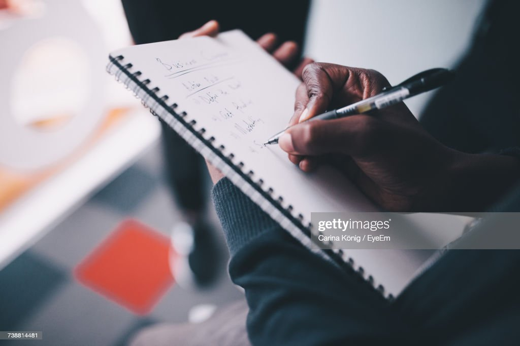 Close-Up Of Woman Hand Holding Notebook : Stock Photo