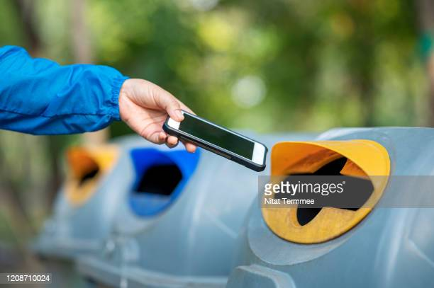 close-up of woman hand throwing smartphone in litter bin outdoors. - electrical equipment stock pictures, royalty-free photos & images