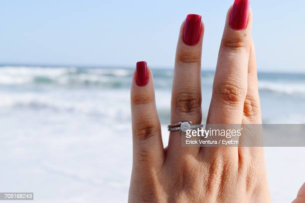 Close-Up Of Woman Hand Wearing Engagement Ring At The Beach