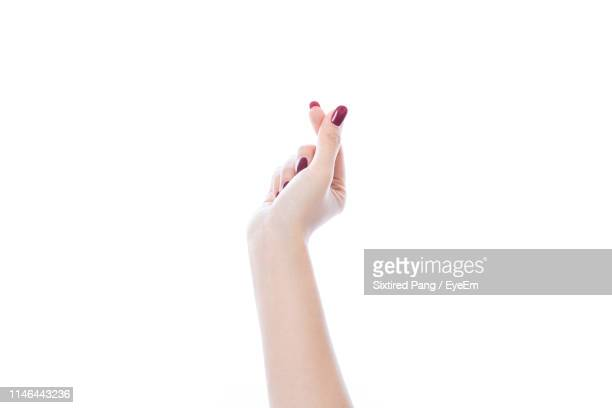 close-up of woman hand wearing red nail polish on fingernails while gesturing against white background - マニキュア液 ストックフォトと画像