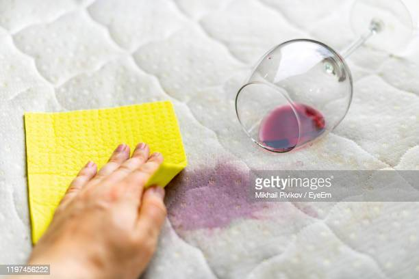 close-up of woman hand wiping wine stains from sofa at home - wine stain stockfoto's en -beelden