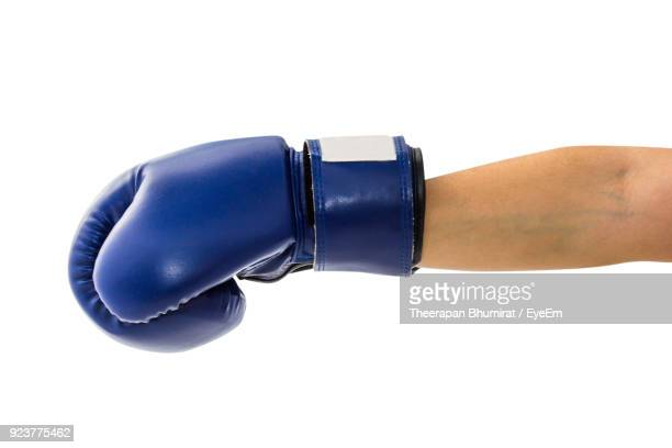 close-up of woman hand with blue boxing glove against white background - boxing gloves stock photos and pictures