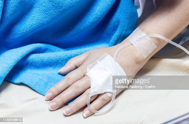 close-up of woman hand with iv drip on bed at hospital - iv drip womans hand stock pictures, royalty-free photos & images